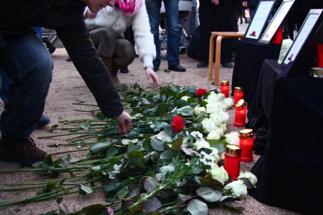 Alle Teilnehmenden legen Blumen nieder